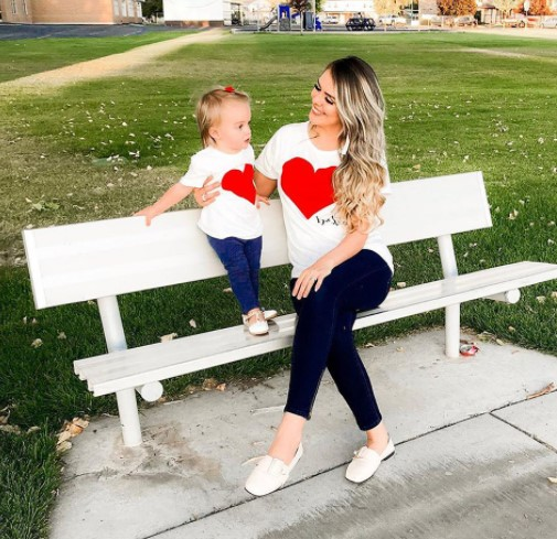 Mother daughter matching outfits-Mother and daughter in matching outfit sitting on a bench.