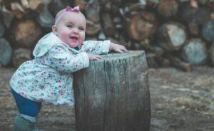 Trends in used baby cloths-Baby IN Jacket standing by tree stump