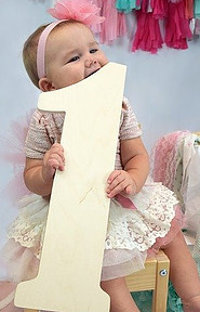 Babies first birthday clothing-Baby putting her teeth in a big number 1 symbol