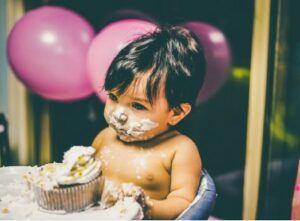 Babies first birthday clothing-Baby enjoying birthday cake