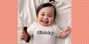 Finn Emma baby clothes-Smiling baby wearing Finn Emma graphic onesie 'Chunky'.