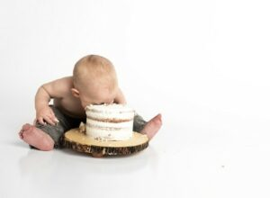 Babies first birthday clothing-Baby eating cake.
