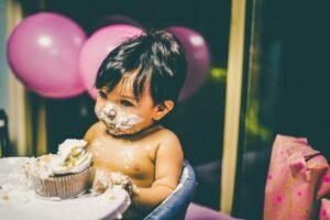 Babies' first birthday clothing-Baby enjoying birthday cake.