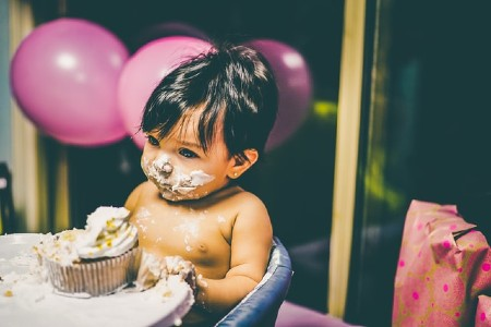 Babies' first birthday clothing-Baby enjoying birthday cake.