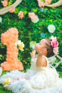 Babies first birthday clothing-Baby girl on first birthday wearing white dress and pink flowers in hair