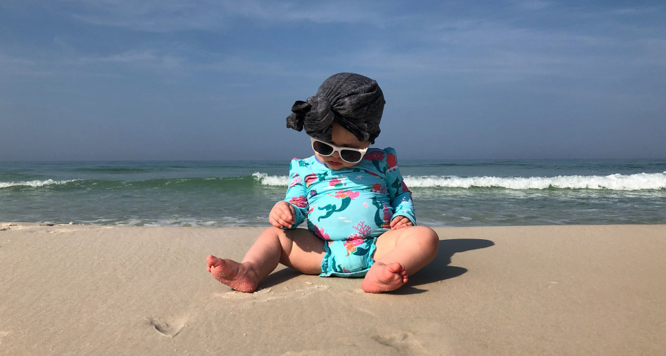Best infant sunglasses-Baby sitting on the beach wearing sunglasses