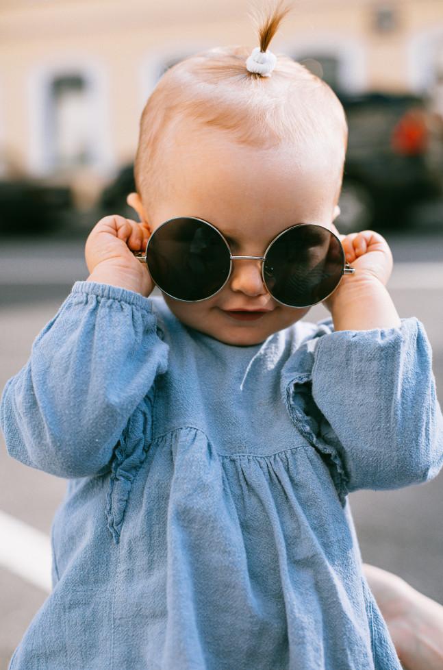 Best infant sunglasses-Baby girl holding sunglasses before her eyes.
