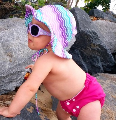 Pea Pod Cloth Nappies-Baby standing by rocks wearing Pea Pod cloth Nappy