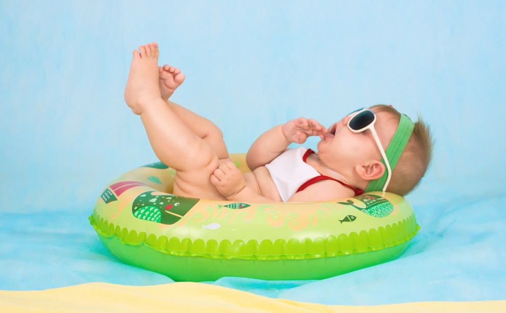 Best infant sunglasses-Baby floating on a doughnut in the water, wearing sunglasses