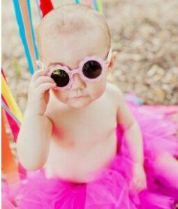 Best Infant sunglasses-Baby in pink tutu holding her sunglasses