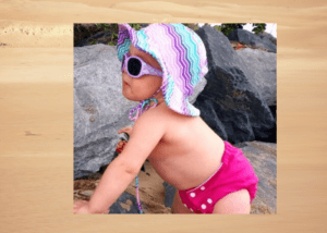 Cancer Council sunglasses review 2020-Baby standing by rocks wearing Cancer Council Sunglasses and a sunhat
