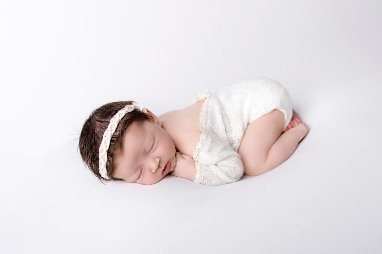 5 benefits organic baby clothes have-baby laying down in white baby suit and hairband.