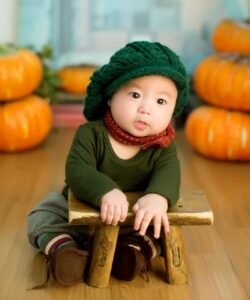 5 Benefits organic baby clothes have-Baby sitting down wearing green outfit