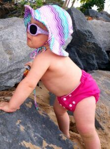 Cancer Council Sunglasses-Baby standing by rocks wearing an sun hat and sunglasses