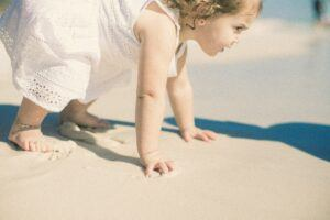 Boutique baby clothes-Baby in a white dress on the beach
