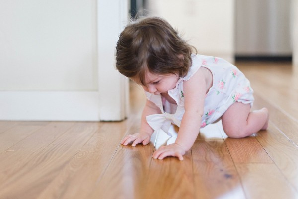 Affordable organic baby clothes in Australia-Baby crawling on a wooden floor.