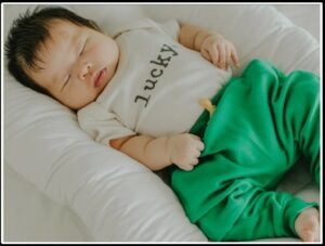 Gender Neutral baby clothes-Newborn baby wearing a lucky bodysuit and green organic trousers.
