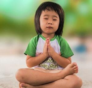 Teaching law of attraction to children-Young child meditating