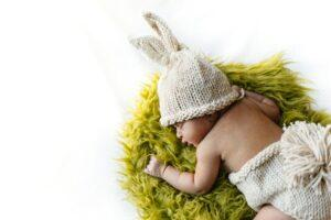 Used baby clothes-Baby laying on a green rug in a cute knitted outfit