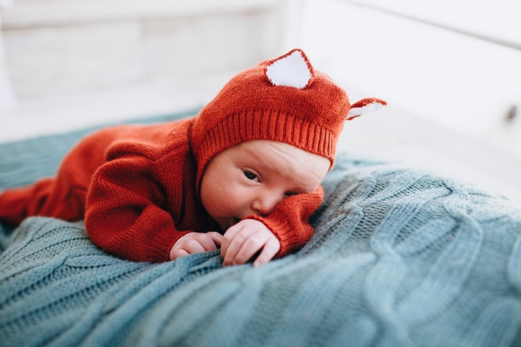 What is gender neutral baby clothing?-Baby wearing cute knitted outfit.