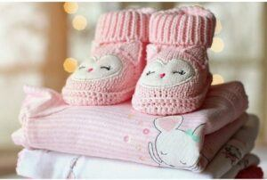 How are cheap baby clothes made?-Pile of baby clothes and shoes on the top.