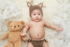 Boutique baby clothes-Baby in cute bunny outfit lays on a rug with a teddy bear