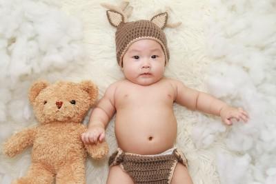 ays on a rug with a teddy bear