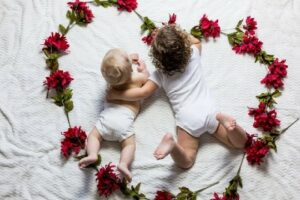 Boutique baby clothes-Baby and toddler laying in white comfortable clothing in a loveheart shape made from flowers