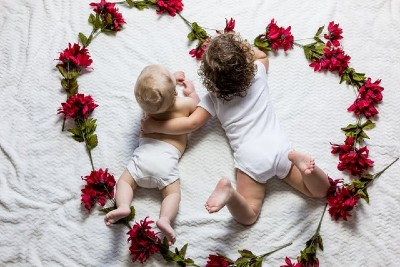 5 Benefits organic cotton have-2 broter in natural clothing laying down in a heart shape made from flowers