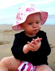 Pea Pod cloth nappies-Bay sitting on the beach wearing Pea Pod Cloth Nappy