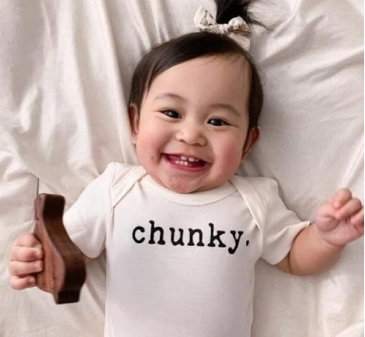 Finn Emma baby clothes-Smiling baby wearing graphic onesie 'Chunky'.