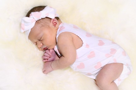 Best baby clothes online- Baby laying down on a rug wearing an Oeko-Tex certified pink love heart outfit.