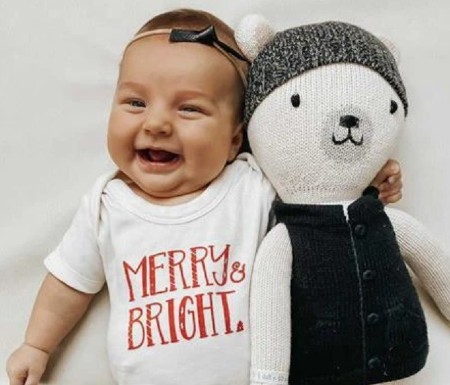 Best Organic Christmas onesies for infants- Happy baby wearing a organic Christmas onesie 'Merry @ Bright.