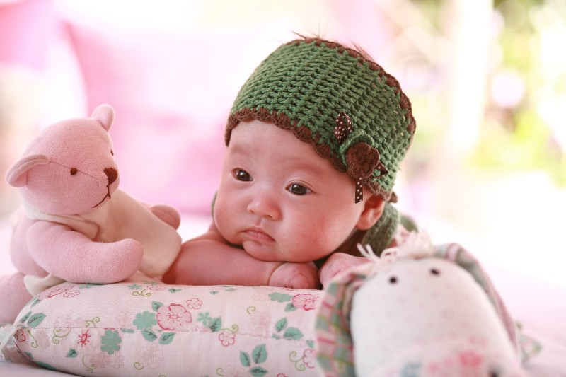 Organic baby clothes for girl's-Baby resting chin on arm wearing a dark green headband.