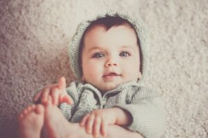 Would you consider renting the baby clothes for a newborn?-Baby in cute knitted outfit.