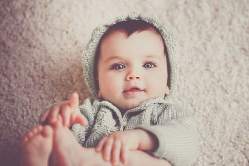 Would you consider renting the baby clothes for a newborn baby?-Baby wearing a cute knitted outfit with hat.