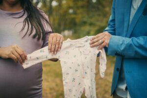 Would you consider renting the baby clothes for a newborn?-Parents to be holding a newborn baby suit.