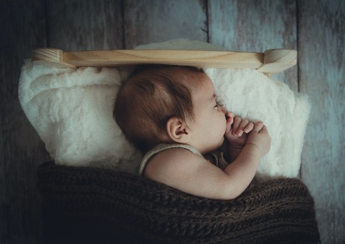 Would you consider renting the baby clothes for a newborn?-Baby sound a sleep in a wooden bed and a white pillow and brown knitted blanket.