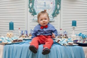 Babies' first birthday clothing-Cute baby sitting on the table on his first birthday-Baby on his firstbirthday sitting on the snack table.