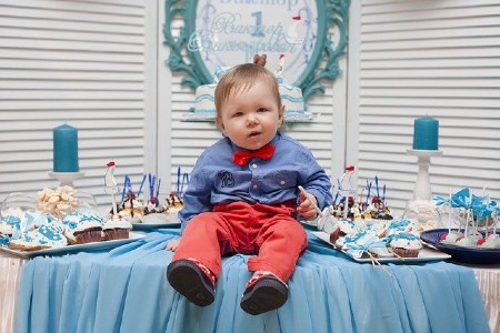 Babies' first birthday clothing-Cute baby sitting on the table on his first birthday.