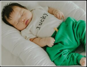 Trendy baby clothes for boys-Baby wearing gender neutral organic outfit with graphic stating 'lucky'.