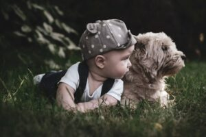 Trendy baby clothes for boys-Baby boy laying on tummy in the grass next to a puppy dog.