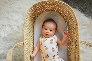 Trendy baby clothes for boys-Baby in crib wearing a bodysuit with orange print.