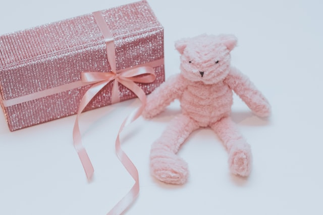 What's the best baby shower gifts?-Nice wrapped gift with pink ribbon and soft toy sitting next to the pressie.