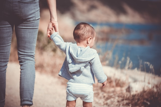Trendy baby boy clothes-Baby boy wearing white shorts and grey hoody while walking along side a bigger person.