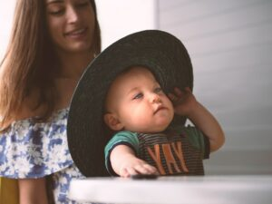 Trends in baby clothes for boys-Baby bioy wearing green shirt with letter print and broad brimmed sun hat.