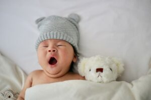 5 benefits organic baby clothes have?-Yawning baby in bed with soft toy and grey hat on.