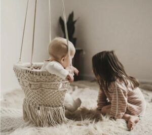 Organic cotton baby's swings-Baby in macramé baby swing with older child on a rug on the side.