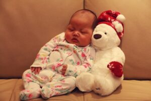 What's Simple Joys by Carter's?-Cute baby leaning against a white teddy bear with closed eyes.