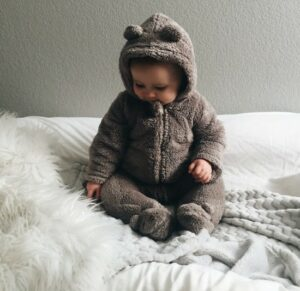 What is gender neutral baby clothing?-Baby sitting on a white rug in a cute gender neutral outfit.